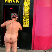 A naked man pauses before heading into Mack Folsom Prison Sex Club in San Francisco after the Folsom Street Fair. The Folsom Street Fair in San Francisco, California, is known as the world's largest Leather Fair, an event marked by participants dressed in outrageous leather, rubber, and fetish attire. Over 300,000 people come to San Francisco for the Folsom Street Fair - making it one of the largest public events in California. The event caps off Leather Week - a seven-day event spotlighting leather and kink. Each year, the week before Folsom Street Fair is filled with motorcycle rides, the Leather Walk, special events, sex parties and other activities.