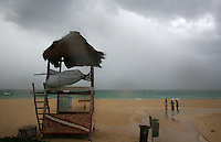 Beach goers brave the wind and rain on the coast of Playa Del Carmen, Mexico during a heavy storm that came through the area in May of 2007.