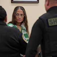 Deborah Green, 71, looks to the doorway of the courtroom  as authorities take her into custody. The trial was held at the Thirteenth Judicial District Court Wednesday afternoon in Grants.