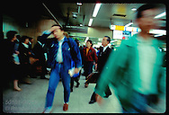 Young man wipes forehead as he rushes among crowd in depths of Tokyo Station. Japan
