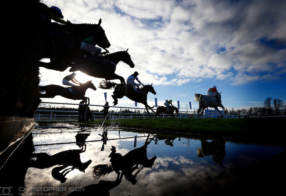 Paddy Brennan on Parsnip Pete (4) leaps the water with the field before winning the Burges Salmon Novices' Handicap Steeple Chase on the first day of the Winter Festival at Newbury Racecourse in Berkshire.