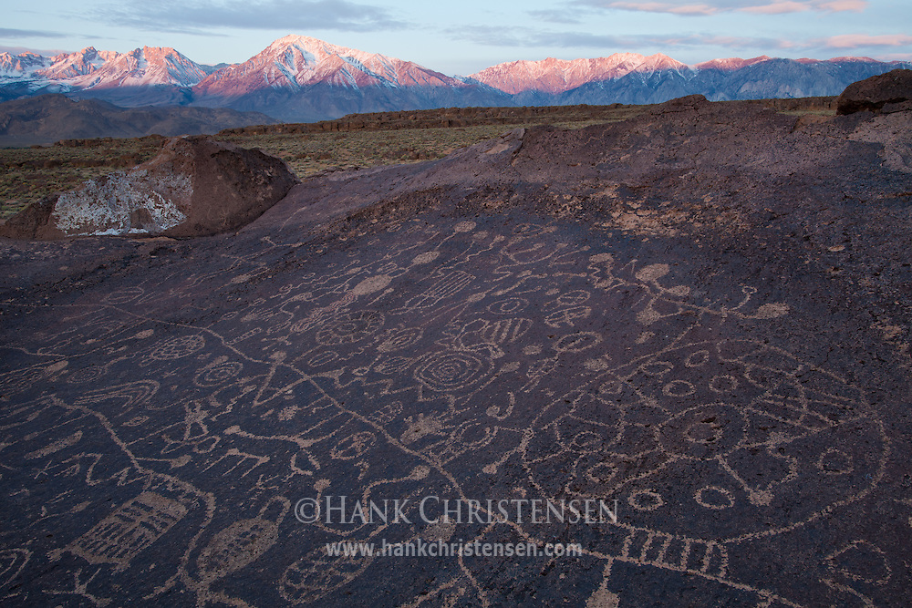 The mountains of the eastern Sierra Nevada glow red over the Sky Rock Petroglyph, just outside of Bishop, CA. Some have theorized that it was probably created by the ancestors of what are today known as the Owens Valley Paiute, possibly as long as 8,000 years ago.