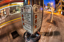Fisheye lens photo of crossing signal sign and buttons at 11th and Main, downtown Kansas City, MO.