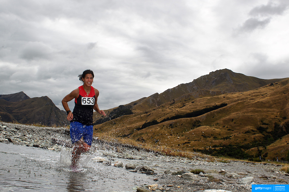 Runner Sofia Stewart crosses Moke Creek on the Ben Lomond High Country Station during the Pure South Shotover Moonlight Mountain Marathon and trail runs. Moke Lake, Queenstown, New Zealand. 4th February 2012. Photo Tim Clayton
