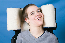 Young woman with Cerebral Palsy whose chair has a fur covered head rest for protection,