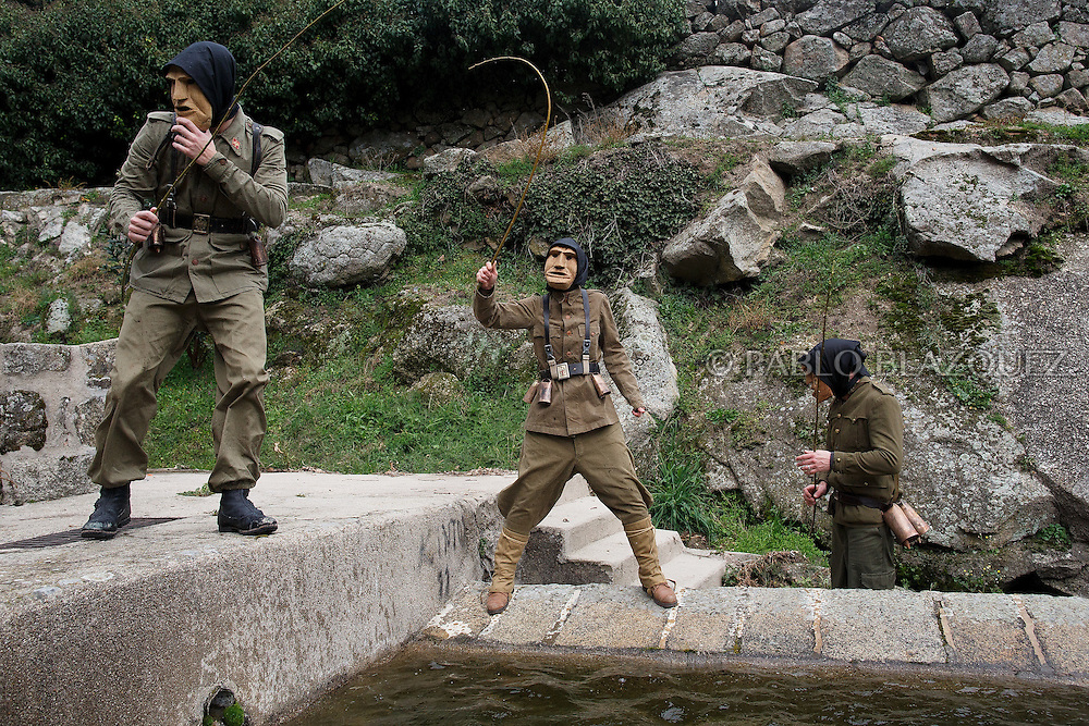 The Machurreros from Pedro Bernardo stand around a fountain and hit the water during Carnival on February 6, 2016 in Pedro Bernardo, in Avila province, Spain. The origins of this pagan festival are unknown. The Machurreros wear wood masks, a military dress, black handkerchief, cowbells, and hold wicker stick. The festival disappeared after Dictator Franco forbid carnival festivals in 1937, but it was recently recovered. Before disappearing, male villagers after the military service, used to dress as Machurreros as they run along the streets scaring children and adults with their wicker stick to bring fertility to the land and expel the evil spirits. (© Pablo Blazquez)