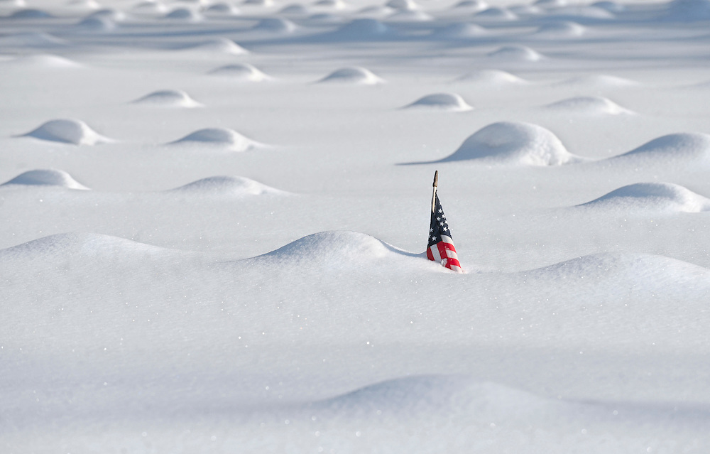 A flag pokes above the snow in around mounds of covered grave markers in Veterans Memorial Field in East Hartford, Conn., after another winter storm. (AP Photo/Jessica Hill)