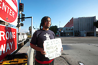 Homeless person with placard standing on street
