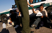 An illegal alien signs paperwork after being apprehended by the U.S. Border Patrol in the desert near El Centro, Calif. on Wednesday, March 30, 2005. Mexican illegal aliens have the choice to return to Mexico after being captured by the U.S. Border Patrol. Most choose this option and are back in Mexico within a few hours.<br />