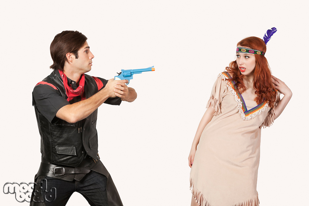 Young cowboy aiming gun at woman in old-fashioned costume against gray background