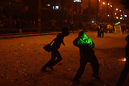 Cairo, Egypt, Dec. 5, 2012-In the light of a green laser, a Muslim Brotherhood supporter of President Mohamed Morsi prepares to throw a rock at opposition protesters as the two sides clashed near the presidential palace. Protesters use the lasers to try to blind their opponents. They also use gas masks to overcome tear gas fired by police. Until now, the two sides have mostly held separate protests; the clashes have only escalated tensions. (Photo by Miguel Juarez Lugo)