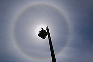 Two birds sitting on street lamp and Solar Halo circle of refracted light in ice crystals around sun and blue sky and clouds.