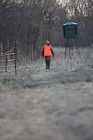 HUNTER WEARING BLAZE ORANGE WALKING TO AN ELEVATED BLIND