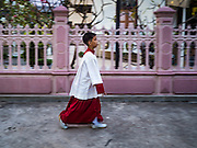 25 MARCH 2016 - BANGKOK, THAILAND: An altar boy walks to Santa Cruz Church before Good Friday observances at the church in Bangkok. Santa Cruz was one of the first Catholic churches established in Bangkok. It was built in the late 1700s by Portuguese soldiers allied with King Taksin the Great in his battles against the Burmese who invaded Thailand (then Siam). There are about 300,000 Catholics in Thailand, in 10 dioceses with 436 parishes. Good Friday marks the day Jesus Christ was crucified by the Romans and is one of the most important days in Catholicism and Christianity.      PHOTO BY JACK KURTZ