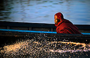 A monk in a boat in a hurry at sunset on Inle lake, Myanmar.