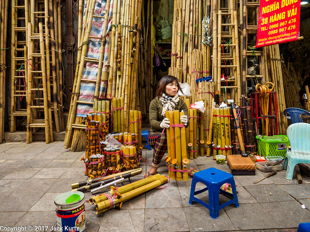 """24 DECEMBER 2017 - HANOI, VIETNAM: A woman sets out traditional Vietnamese pipes she sells in her bamboo shop in the old quarter of Hanoi. The old quarter is the heart of Hanoi, with narrow streets and lots of small shops but it's being """"gentrified"""" because of tourism and some of the shops are being turned into hotels and cafes for tourists and wealthy Vietnamese.           PHOTO BY JACK KURTZ"""