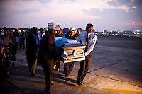 Funeral directors and family members carry the caskets containing the bodies of victims killed by drug cartels, at an Air Force base in Guatemala City , Wednesday, March 21, 2012. The remains of 11 Guatemalan citizens were repatriated from Mexico on Wednesday. 193 bodies found in Tamaulipas state of the northern Mexico in 26 mass graves in April 2011. Mexican authorities believe the dead were mostly migrants kidnapped from buses and killed by the Zetas drug cartel.