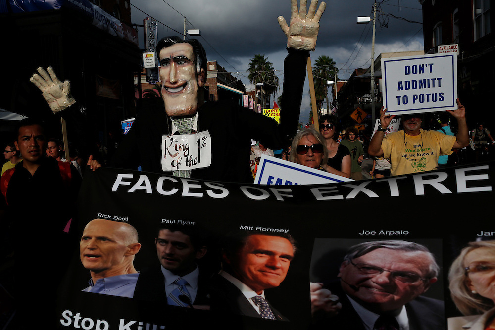 Protesters march through the streets of Ybor City with an oversized puppet of Mitt Romney, the GOP candidate for president, for a voter's suppression march during the 2012 Republican National Convention on August 28, 2012.