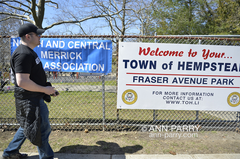 North Merrick, New York, USA. March 31, 2018. LOU CICCONE, Co-Pesident of North and Central Merrick Civic Association (NCMCA), removes NCMCA sign from Fraser Park fence at the end of the Annual Eggstravaganza.