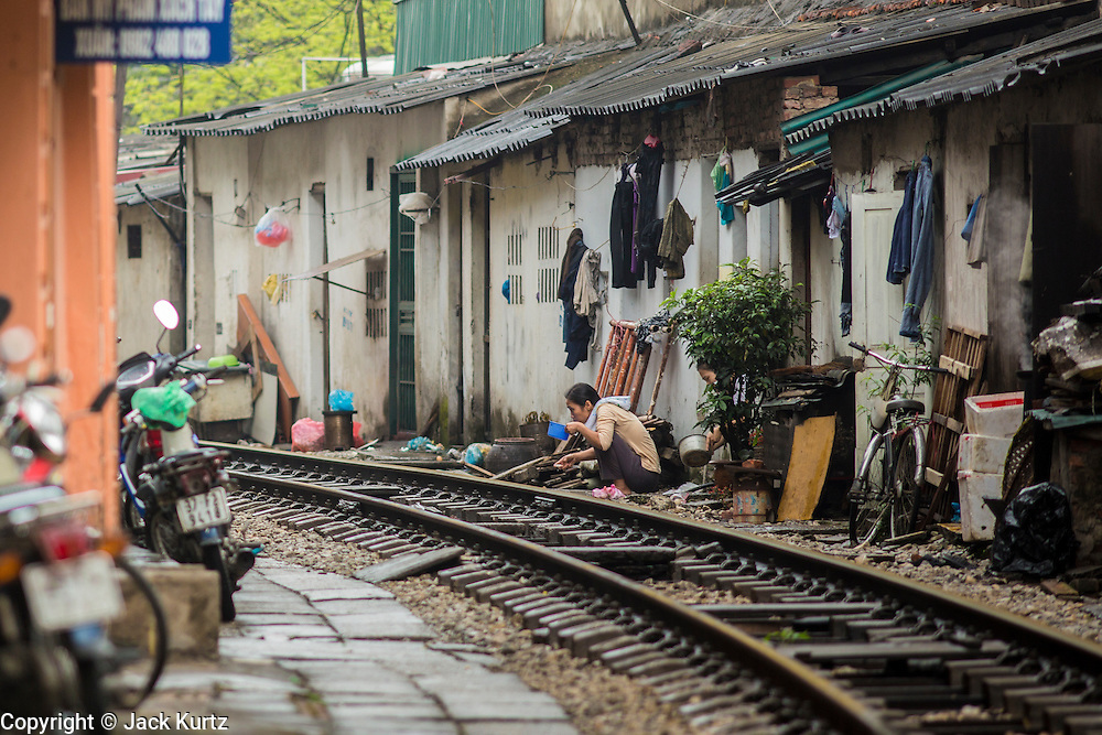 07 APRIL 2012 - HANOI, VIETNAM: A woman brushes her teeth on the train tracks in Hanoi, the capital of Vietnam. Hanoi is one of the oldest cities in Southeast Asia. It was established in 1010 A.D.   PHOTO BY JACK KURTZ