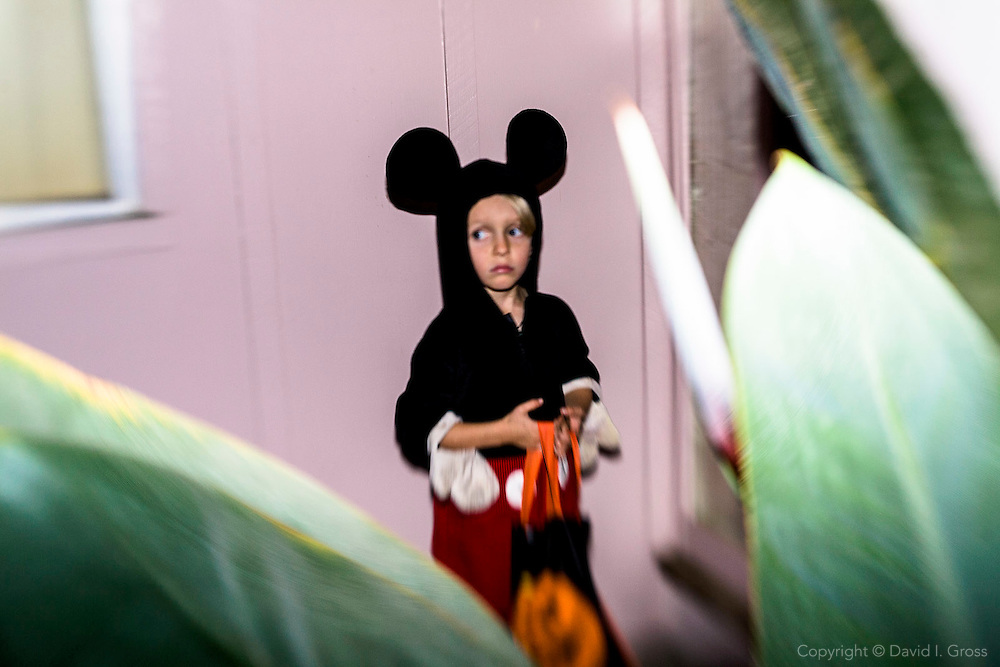 Nicolas Lux waits nervously for his siblings to arrive before knocking on a door to ask for candy. While he knows some of his close neighbors, those living more than a block away are strangers.