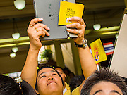 05 DECEMBER 2014 - BANGKOK, THAILAND: A man takes a picture with his tablet device as he walks into the plaza of Siriraj Hospital on the birthday of Bhumibol Adulyadej, the King of Thailand. Thais marked the 87th birthday of the King Friday. The revered Monarch was scheduled to make a rare public appearance in the Grand Palace but cancelled at the last minute on the instructions of his doctors. He has been hospitalized in Siriraj Hospital, across the Chao Phraya River from the Palace, since early October.    PHOTO BY JACK KURTZ