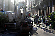In Amsterdam loopt een vrouw met een wandelwagen en een jongetje op een driewieler langs een graafmachine.<br /> <br /> In Amsterdam a woman with a stroller and a boy on a tricycle passes an excavator.