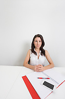 Portrait of confident businesswoman with cell phone and binder at desk in office