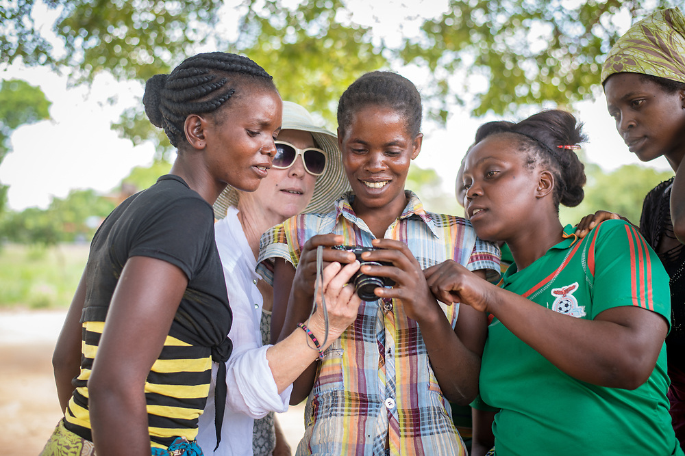 A group of women gather together to view something on a camera in Livingstone, Zambia