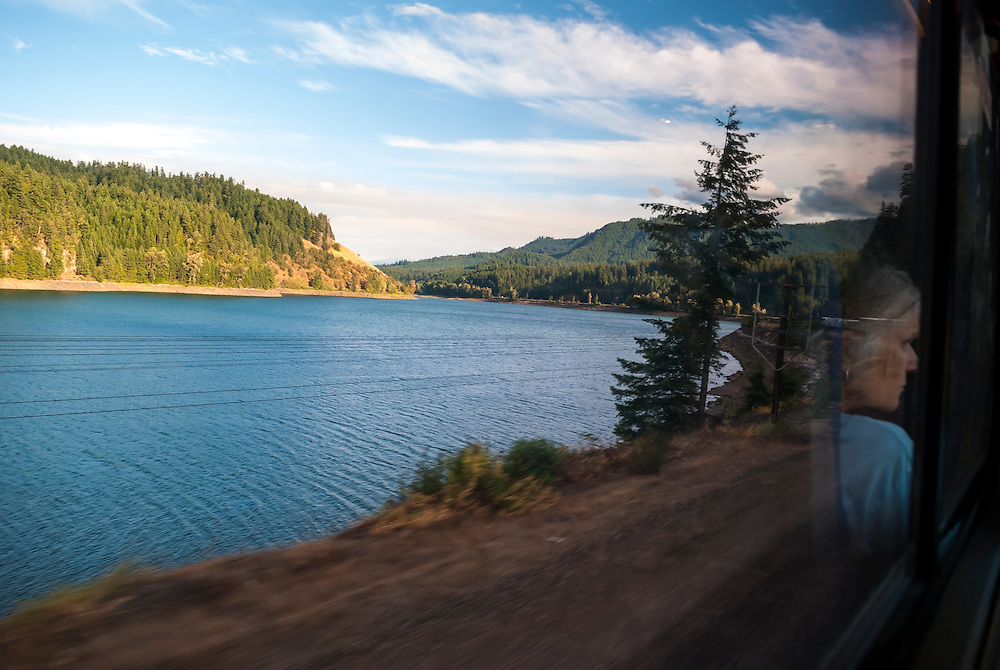 Reflection of a women in a window on an Amtrak train traveling through scenic landscape in southern Oregon