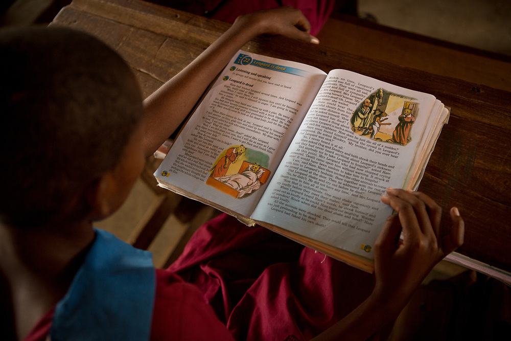A schoolgirl reads a story book at a school in Samburu