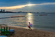 "26 SEPTEMBER 2014 - PATTAYA, CHONBURI, THAILAND: A vendor who sells toys walks along Pattaya Beach at the end of the day. Pataya, a beach resort about two hours from Bangkok, has wrestled with a reputation of having a high crime rate and being a haven for sex tourism. After the coup in May, the military government cracked down on other Thai beach resorts, notably Phuket and Hua Hin, putting military officers in charge of law enforcement and cleaning up unlicensed businesses that encroached on beaches. Pattaya city officials have launched their own crackdown and clean up in order to prevent a military crackdown. City officials have vowed to remake Pattaya as a ""family friendly"" destination. City police and tourist police now patrol ""Walking Street,"" Pattaya's notorious red light district, and officials are cracking down on unlicensed businesses on the beach.     PHOTO BY JACK KURTZ"