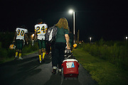 "BIRMINGHAM, AL – SEPTEMBER 11, 2015: Sonya Whitaker walks to the buses with the Woodlawn High School football team following a game. As a type 1 diabetic, Quintarius Monroe requires frequent blood sugar testing and supervision when self-administering insulin. When care from qualified personnel at his school in Center Point became unavailable, Monroe was forced to transfer several miles away from his locally zoned school to attend Woodlawn High School. The Americans with Disabilities Act requires schools to provide ""reasonable accommodation"" for students with medical conditions, but given that most schools no longer retain school nurses, many schools are failing to provide adequate care for their students.<br />
