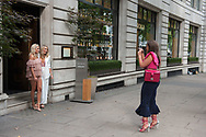 London, 12/08/2017: escort taking a picture outside a japanese restaurant, Strand.<br /> &copy; Andrea Sabbadini