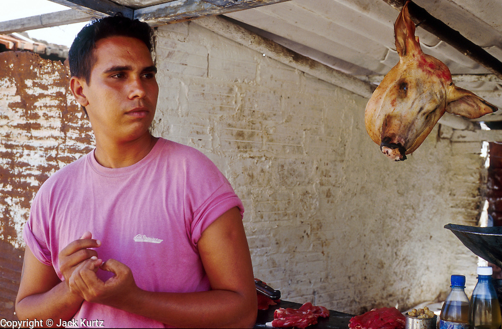 23 JULY 2002 - TRINIDAD, SANCTI SPIRITUS, CUBA: A butcher waits for customers the colonial city of Trinidad, province of Sancti Spiritus, Cuba, July 23, 2002. Trinidad is one of the oldest cities in Cuba and was founded in 1514..PHOTO BY JACK KURTZ