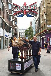 **CAPTION CORRECTION - Rhino statues are 750mm tall, not 750cm tall, as stated in previous captions**<br /> © Licensed to London News Pictures. 20/08/2018. LONDON, UK. Technicians transport a rhino painted by The Chapman Brothers to a photocall in Carnaby Street.  At 750mm tall and weighing 300 kg, each rhino has been specially embellished by an internationally renowned artist.  21 rhinos are in place at a popular location in central London, forming the Tusk Rhino Trail, until World Rhino Day on 22 September to raise awareness of the severe threat of poaching to the species' survival.  They will then be auctioned by Christie's on 9 October to raise funds for the Tusk animal conservation charity.  Photo credit: Stephen Chung/LNP