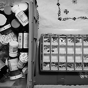 Maria organizes Ricky's pills.  The financial stress of caring for a paralyzed individual can inflict incredible amounts of debt.  Often fundraisers and aid from non-profit organizations are required to help diffuse the costs.  Ricky needs many different forms of medication in order to mitigate pain and other ailments like muscle spasms that are associated with prolonged paralysis.
