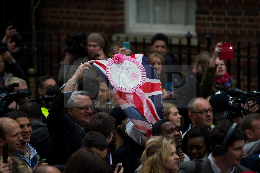 """© London News Pictures. 02/05/2015. A fan holding a sign reading """"It's a Girl"""" as Catherine Duchess of Cambridge and Prince William leave the Lindo Wing of St Mary's hospital in London holding their new born baby daughter, Princess of Cambridge. Photo credit: Ben Cawthra /LNP"""