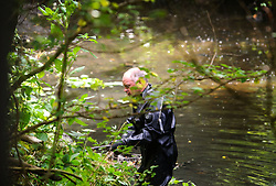 © Licensed to London News Pictures. 24/07/2013 London, UK. A member of the Underwater and Confined Space Search Unit checks along a stream investigating the murder of a young Hungarian national who's body was found in a suitcase on Sunday (July 21st). A 29 year old has been arrested on suspicion of murdering the young woman found dead in Thornfield Avenue, North West London.<br /> Photo credit : Simon Jacobs/LNP