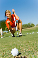 Female golfer looking at ball rolling towards cup focus on ball