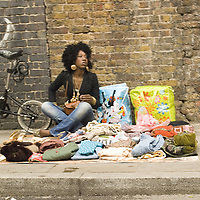 Afro-caribbean young woman selling second hand clothes, Brick lane market, London<br />