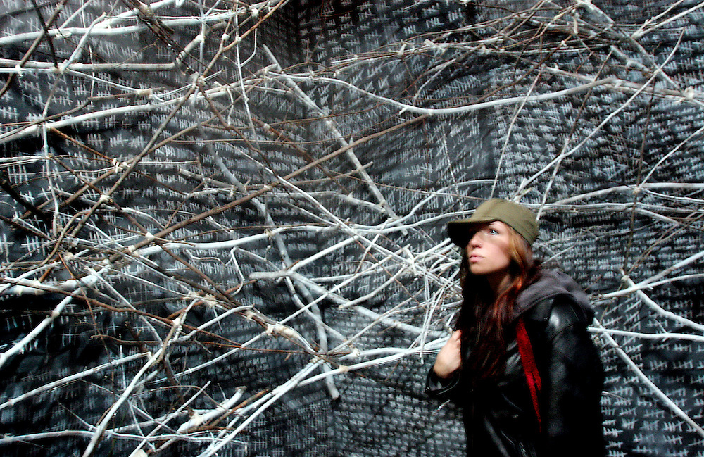 "12/01/05 Boston, MA-- Carissa Jope, 21, of Wenham, looks around inside a room designed like a nest, part of the ""Medicine Wheel"" installation at the Cyclorama in honor of World AIDS Day Thursday.  (120105aidsar01, saved in fri, Staff Photo by Angela Rowlings)"