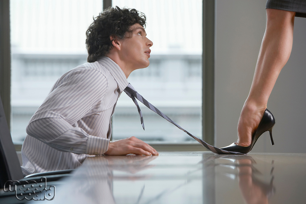 Businesswoman standing on desk stepping on businessman's tie side view