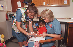 Two nurses examining young girl's arm,