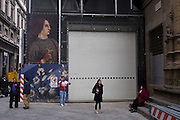 Tourists beneath renaissance art construction poster  in Florence's Piazza degli Uffizi. .