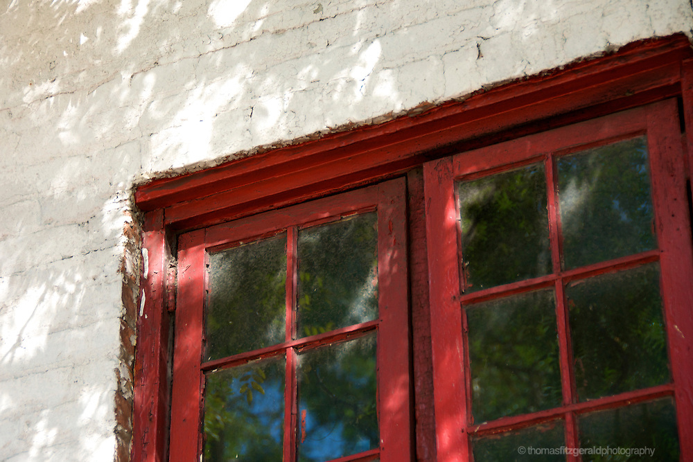 Dappled sun plays on this old red painted glass doorway
