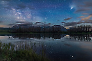 Jupiter (at right) and Saturn (at left) shining brightly in the sky and reflected in the still waters of Maskinonge Lake at Waterton Lakes National Park, Alberta, on June 17/18, 2018. The Milky Way is at left, Scorpius is at centre, and two satellite trails are at top. The sky is blue with solstice twilight. The trees on the opposite shore are charred from the Kenow Fire in September 2017. In the distance are Sofa Mountain and Viny Peak. <br /> <br /> This is a stack of 10 exposures for the ground, mean combined to smooth noise, and one exposure for the sky and stellar reflections. All 20 seconds at f/2.2 with the Sigma 20mm Art lens and Nikon D750 at ISO 3200.