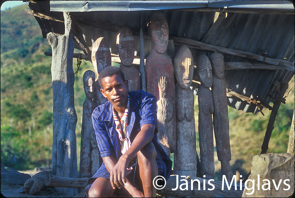 This is the son in front of his fathers waga. Wagas (wakas) are erected for village heros who might have killed a dangerous animal or were great leaders or administrators. Konso tribe, Ethiopia, Africa