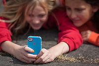 Two teen aged girls share a laugh and a text.
