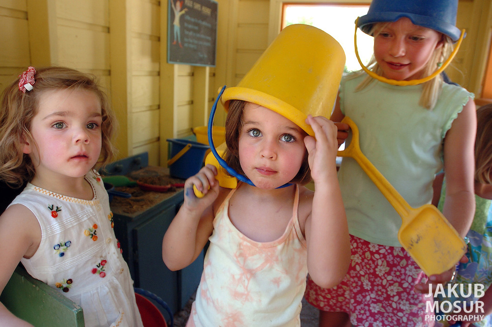 Maggie Livermore, 4, left, Charlotte Carek, 3, wearing a yellow bucket, and Alex Paff, 6, look out from a playhouse at the Pixie Park in Ross, a neighborhood park for kids age 6 and under..Event on 8/31/05 in Ross...JAKUB MOSUR / The Chronicle